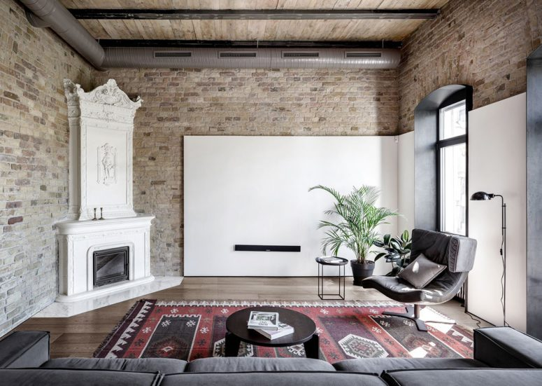 The living room features comfy furniture, a vintage hearth with a built-in modern fireplace and original brick clad