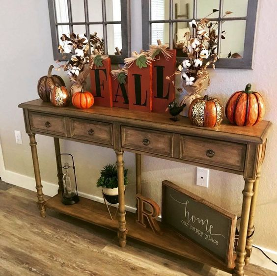 a bright fall console with fake pumpkins, cotton arrangements and wooden letters in bright orange