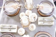 02 a chic neutral table setting with a grey tablecloth, white pumpkins and candles and feathers for each place setting