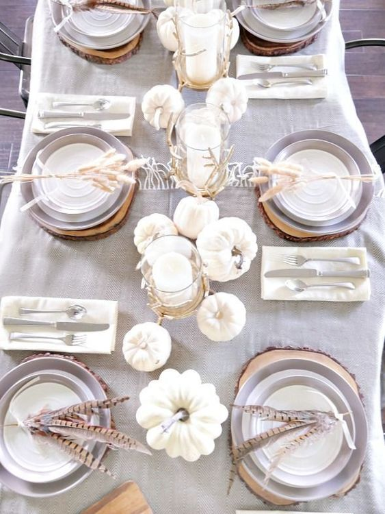 a chic neutral table setting with a grey tablecloth, white pumpkins and candles and feathers for each place setting