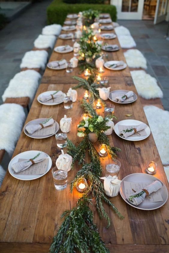 a natural tablescape with a greenery runner, candles in lanterns and napkins, some white blooms for a festive feel