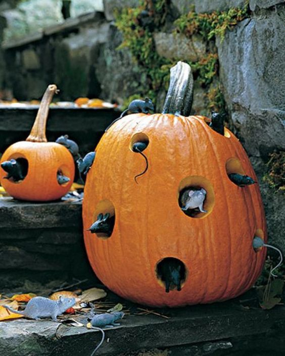a real pumpkin with cutouts and fake mice inside for indoor or outdoor Halloween decor