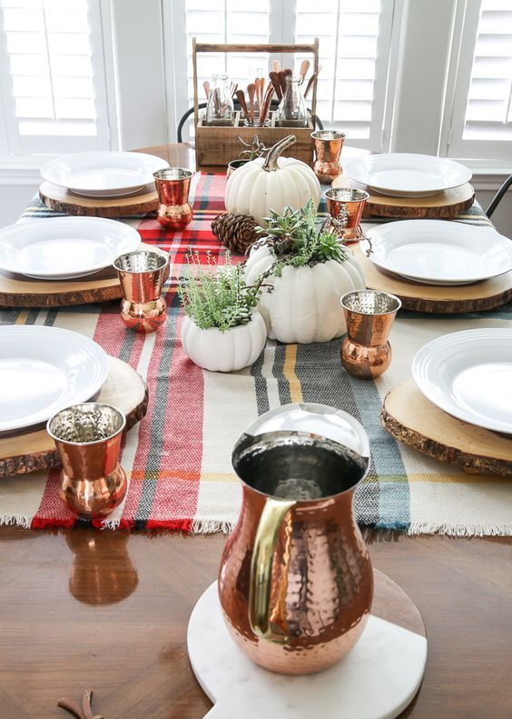 copper glasses of a whimsy shape and a matching pitcher spruce up the simple rustic tablescape