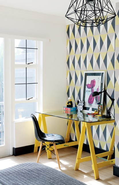 The home office is extremely colorful, with bright wallpaper, artworks and colorful furniture