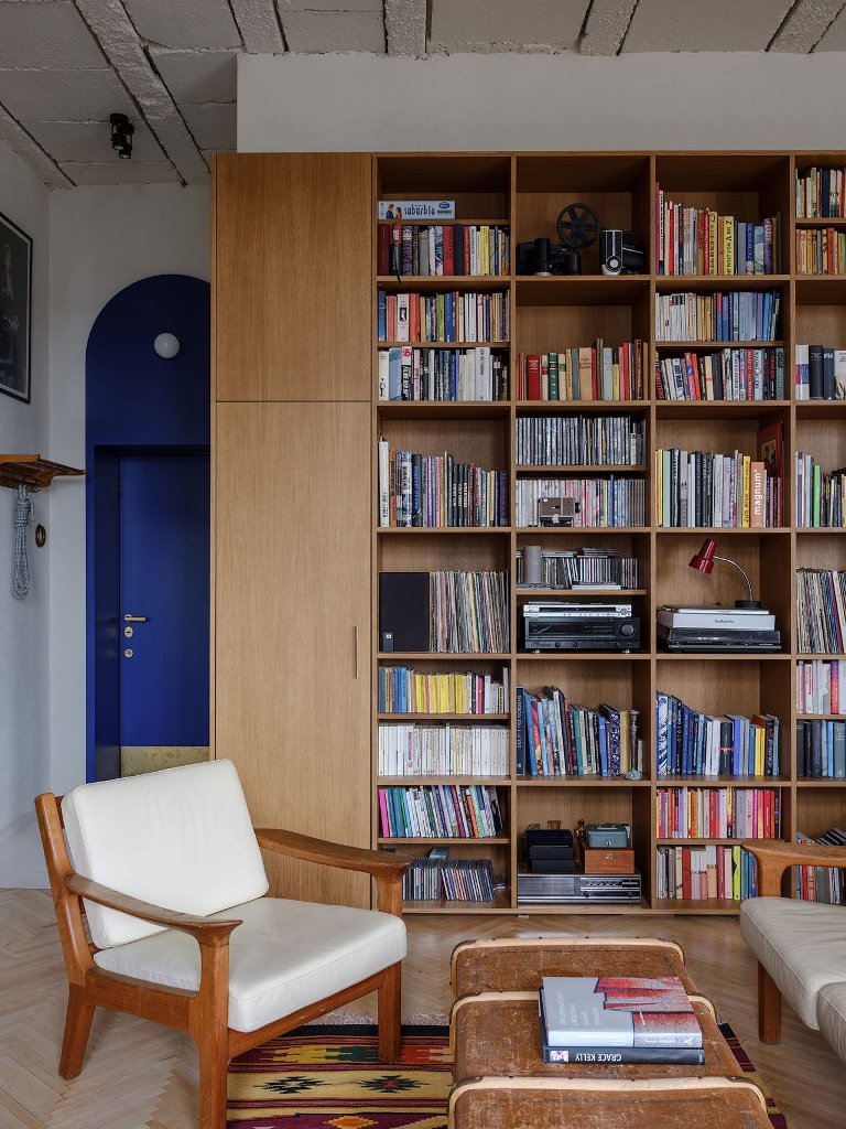 The living room features a large bookshelf, which covers a whole wall