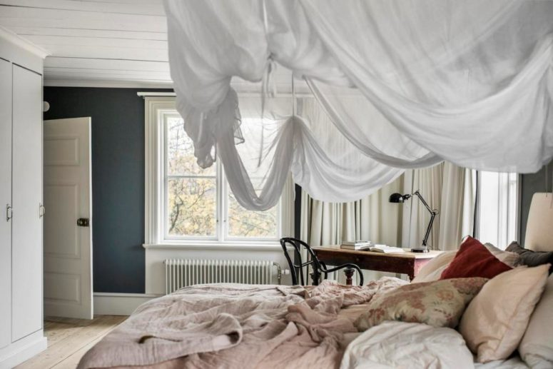 The master bedroom is a peaceful space with a large bed with a suspended canopy and a desk byt the window