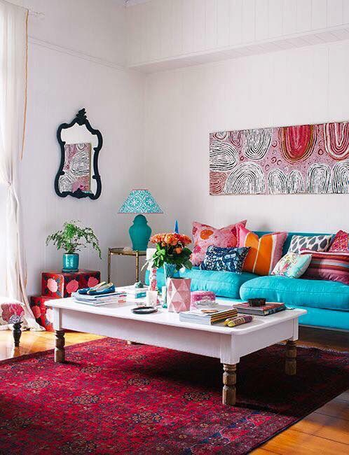 a bold living room with many printed textiles, pillows, artworks and chic furniture