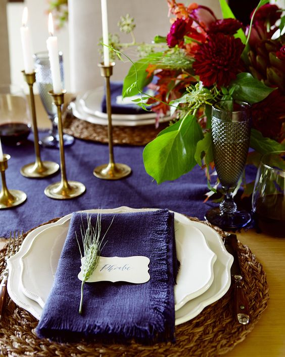 a bold violet table runner and napkins plus burgundy blooms make up a super bright tablescape