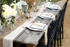 03 a burlap table runner, white blooms with feathers and a large wheat centerpiece with ribbon for a rustic fee