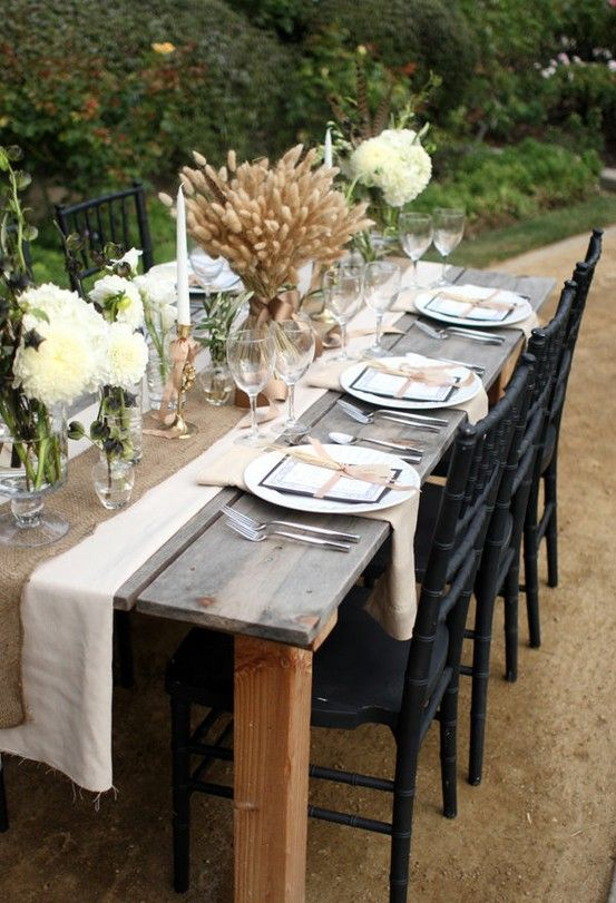 a burlap table runner, white blooms with feathers and a large wheat centerpiece with ribbon for a rustic fee