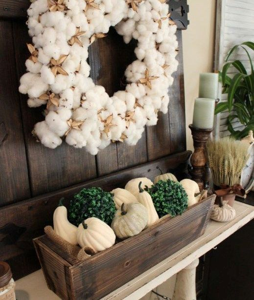a cozy fall console with a cotton wreath and a wooden box with faux pumpkins and gourds and boxwood balls