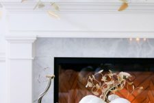 03 a gorgeous thanksgiving mantel with lots of fabric pumpkins with fabric leaves and a fabric pumpkin display next to the fireplace
