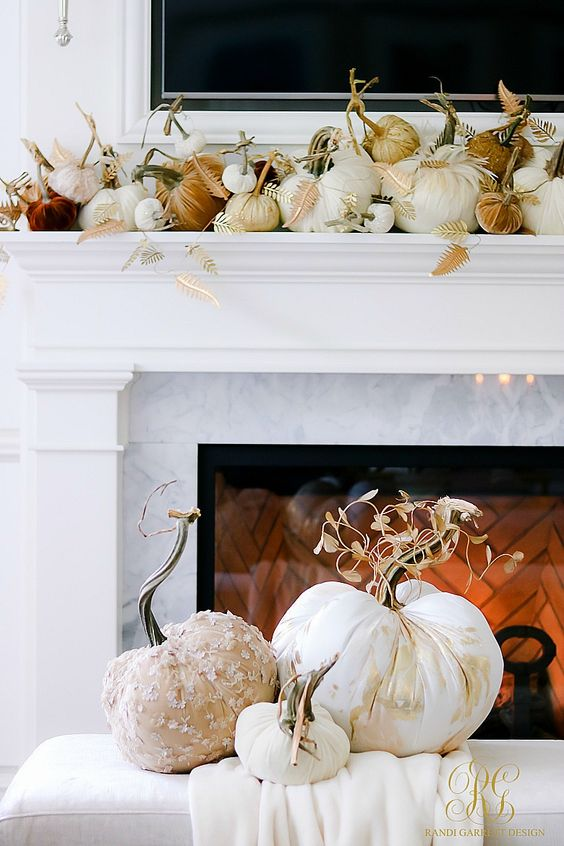 a gorgeous thanksgiving mantel with lots of fabric pumpkins with fabric leaves and a fabric pumpkin display next to the fireplace