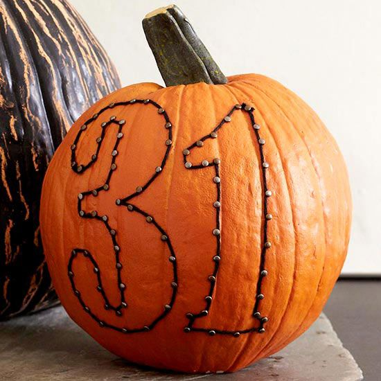 a real pumpkin with art made with decorative nails and yarn is an easy Halloween craft