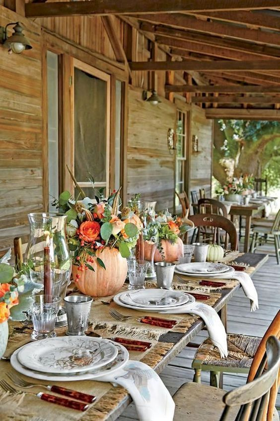 natural fall centerpieces with pumpkin vases, orange blooms, feathers and greenery for Thanksgiving