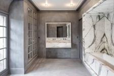 04 The bathroom is luxurious,done in concrete and marble, with French doors, windows and a bathtub