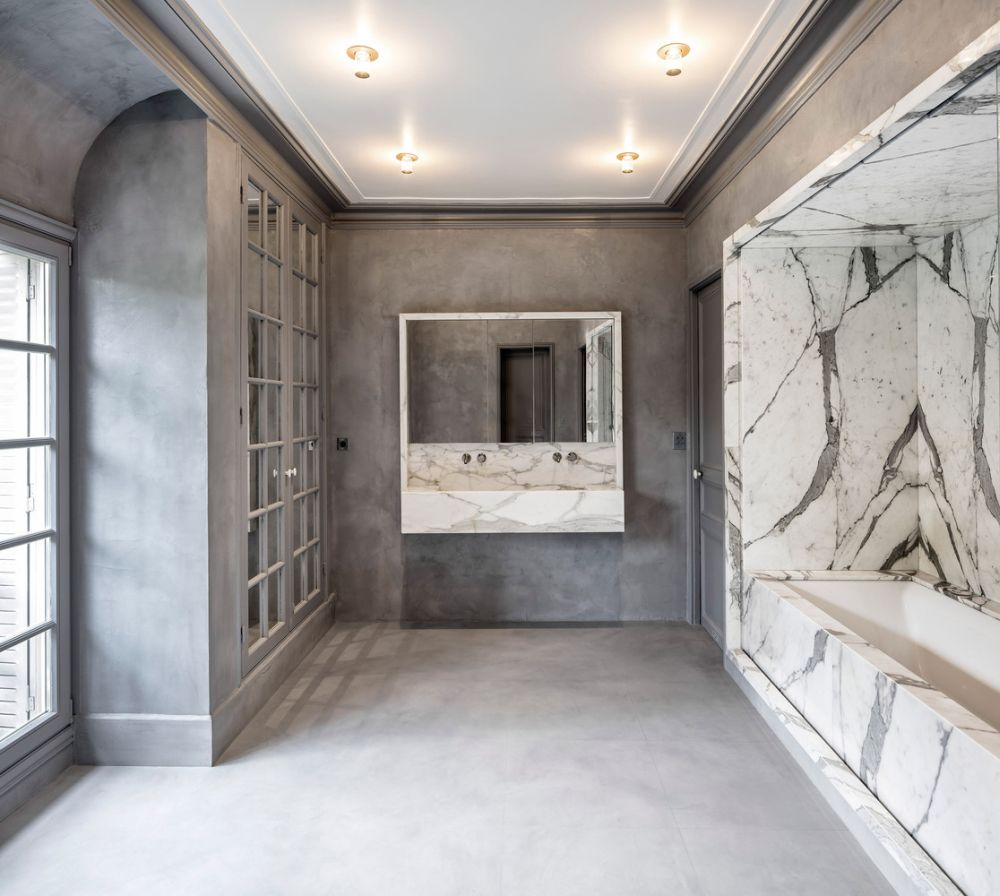The bathroom is luxurious,done in concrete and marble, with French doors, windows and a bathtub