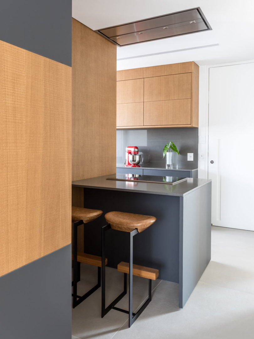 The kitchen features sleek grey surfaces and wood for a contrast, there's a kitchen island with a breakfast nook