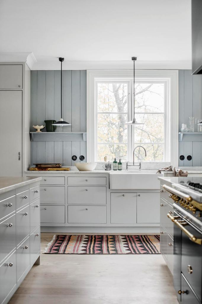 The kitchen is clad with grey wood and off-white cabinets