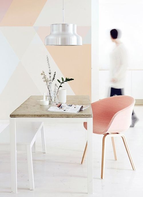 a feminine home office with a geometric color block wall in pastel shades plus a matching pink chair