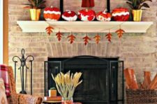 a mantel with colorful pumpkins, a fall leaf banner,potted plants and a faux horse head with a scarf