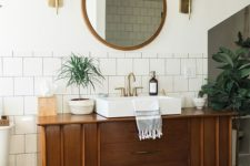 04 a mid-century modern bathroom with subway tiles, a wooden vanity and much potted greenery