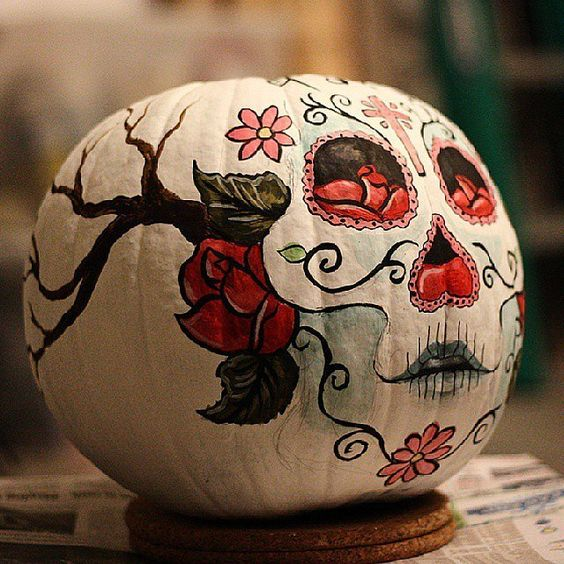 a pumpkin with a painted sugar skull is a nod at the Mexican holiday and a great boho idea for Halloween