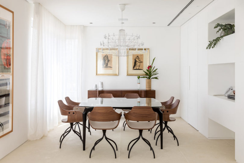 The dining room is done with quirky chairs, cool artworks and a chic chandelier for a statement