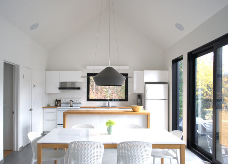 The dining space is done with a white dining table and chairs and is marked with a graphhite grey pendant lamp