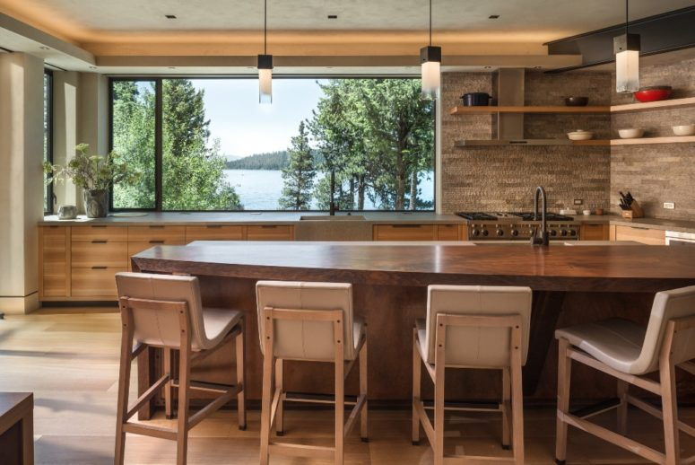 The kitchen features a panoramic window, a large kitchen island and comfy upholstered chairs