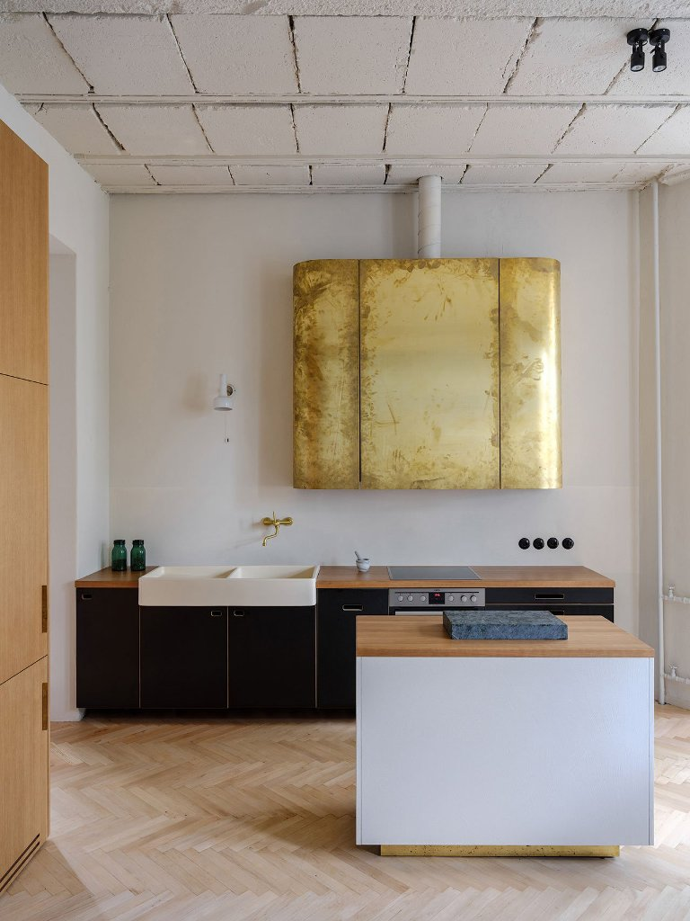 The kitchen is done with dark and light-colored plywood cabinets and look at that gold leaf hood -isn't it a statement