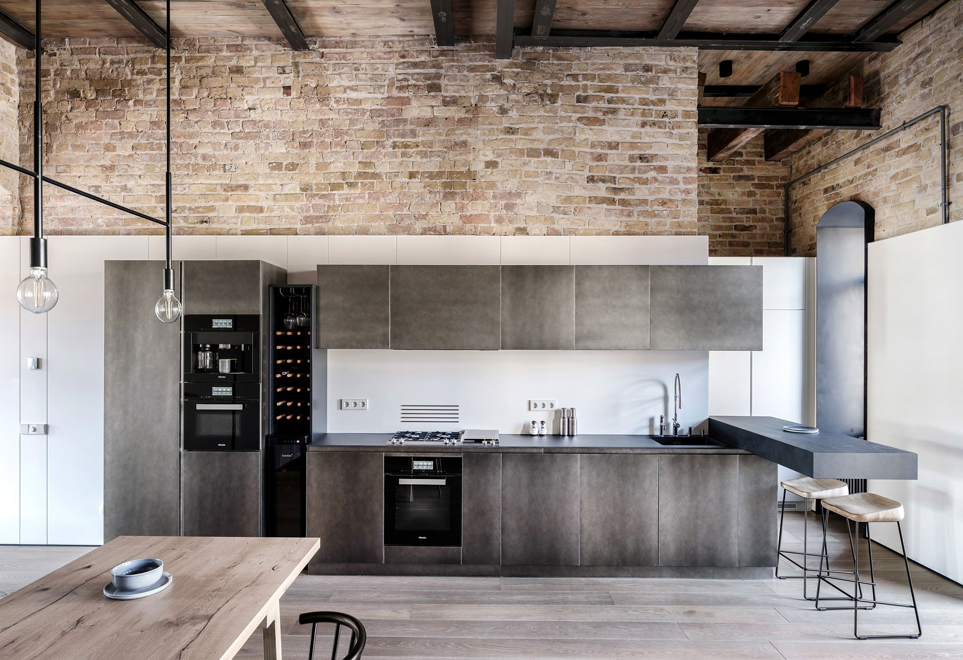 The kitchen is done with dark metal cabinets and a floating breakfast space with stools