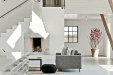 05 The living space features a large fireplace, contemporary and comfy furniture and a stunning chandelier