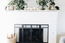 05 a fresh and natural feel given to the mantel with fresh greneery, white pumpkins and lanterns on each side