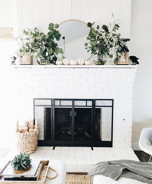 a fresh and natural feel given to the mantel with fresh greneery, white pumpkins and lanterns on each side