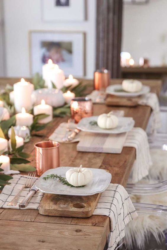 a natural tablescape with cutting boards, white pumpkins, greenery and copper mugs for a chic touch