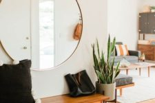 05 an airy mid-century modern entryway with an oversized round mirror and a cool bench