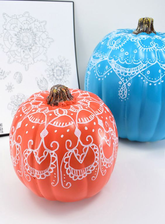 bright pumpkins with henna decor on them to add a colorful touch and a boho feel to the space