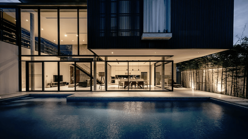 Extensive glazing opens the house to the garden and pool, which are still wrapped with a concrete fence to keep the privacy