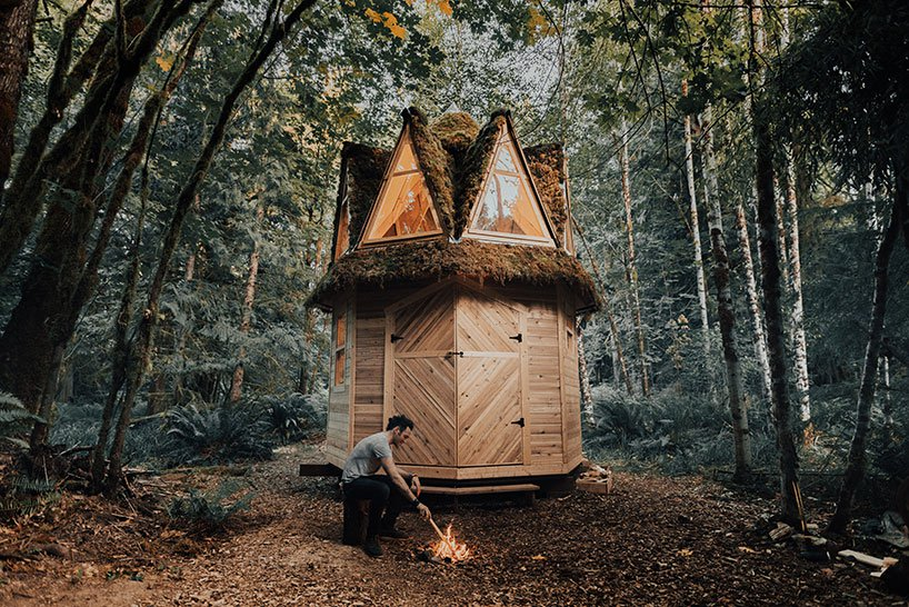 The cabin is placed outside and the owners may make a fire next to it and sit on tree stumps