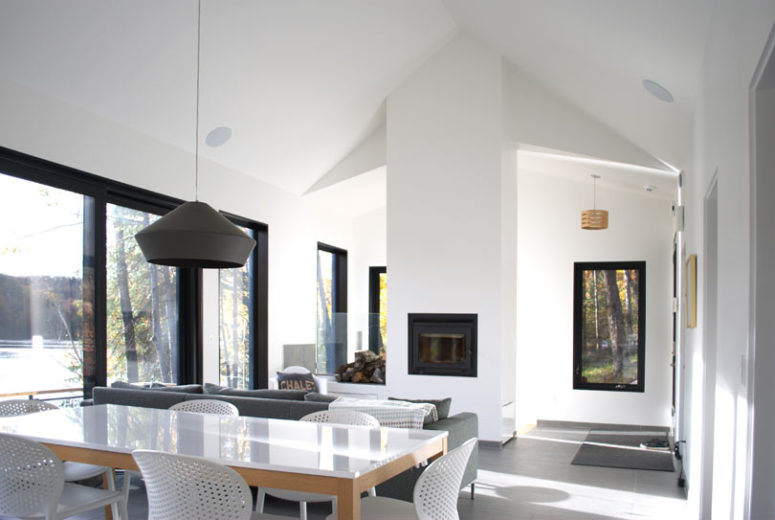 The living room is done with a built-in hearth, a grey sofa and the main thing here is large windows that bring in light