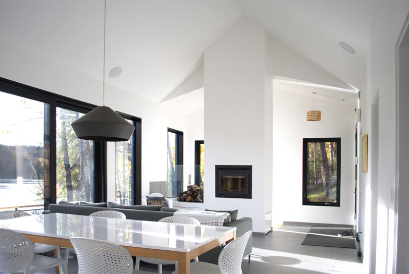 The living room is done with a built in hearth, a grey sofa and the main thing here is large windows that bring in light