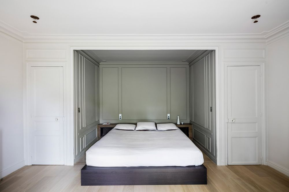 The master bedroom also shows off a niche with wall panelling, a platform bed and a storage headboard