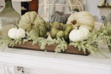 06 a farmhouse styled Thanksgiving decoration of a wooden crate, greenery, white and green pumpkins and a fake cage
