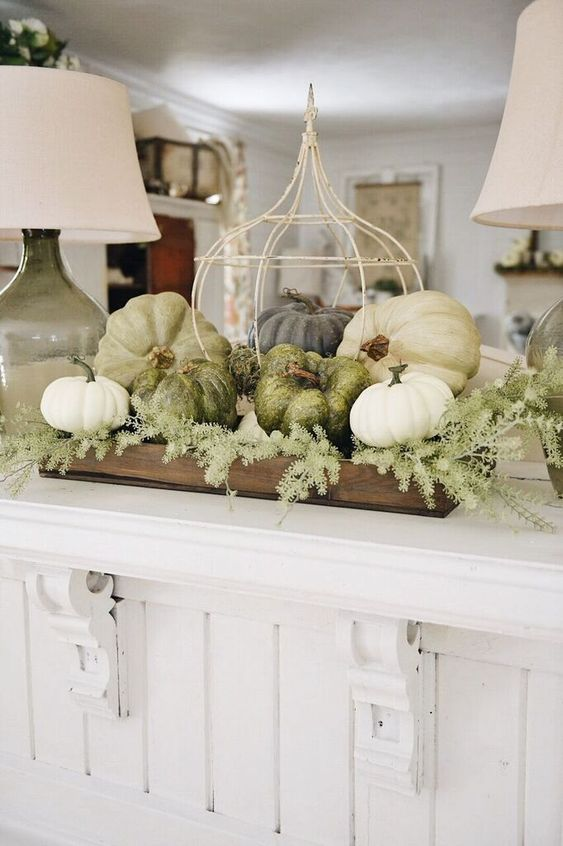 a farmhouse styled Thanksgiving decoration of a wooden crate, greenery, white and green pumpkins and a fake cage