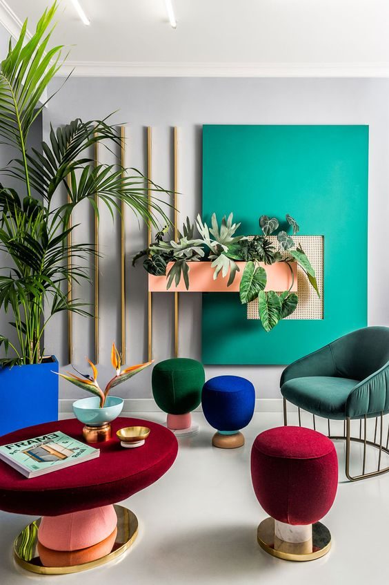 a super colorful space with jewel tone stools and colorful upholstered furniture plus a colorful accent wall