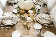 06 a table runner of white burlap, little white and gilded pumpkins, greenery, antlers and LEDs on an uncovered table