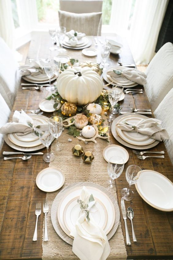a table runner of white burlap, little white and gilded pumpkins, greenery, antlers and LEDs on an uncovered table