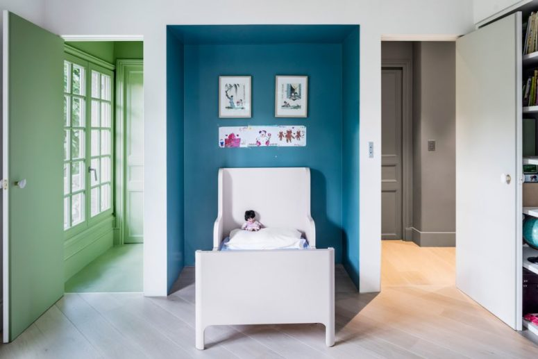 Another kid's bedroom is done with a blue niche, a comfy kid's bed and colorful doors add to the space