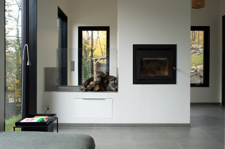 Glass firewood storage is a great idea to add coziness to the space while being useful at the same time